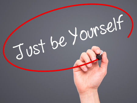 esteemed: Man Hand writing Just be Yourself with black marker on visual screen. Isolated on background. Business, technology, internet concept. Stock Photo Stock Photo