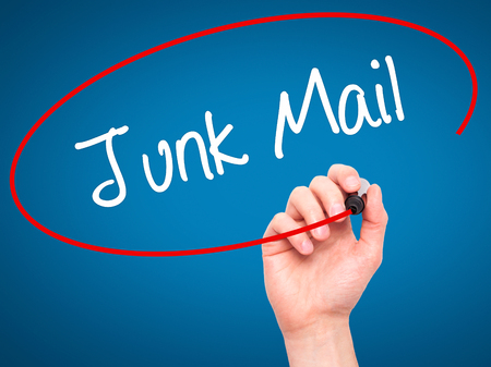 solicitors: Man Hand writing Junk Mail with black marker on visual screen. Isolated on blue. Business, technology, internet concept. Stock Photo