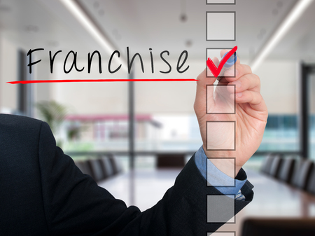 stock listing: Businessman hand writing Franchise and check listing task. Isolated on office background. Stock photo