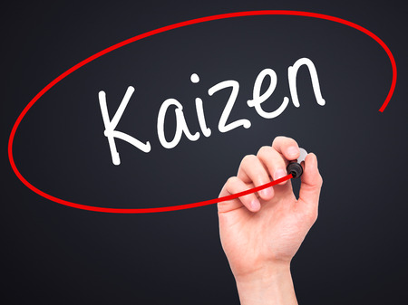kaizen: Man Hand writing Kaizen with black marker on visual screen. Isolated on black. Business, technology, internet concept. Stock Photo