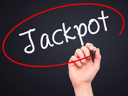 Man Hand writing Jackpot with black marker on visual screen. Isolated on background. Business, technology, internet concept. Stock Photo