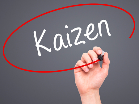kaizen: Man Hand writing Kaizen with black marker on visual screen. Isolated on grey. Business, technology, internet concept. Stock Photo