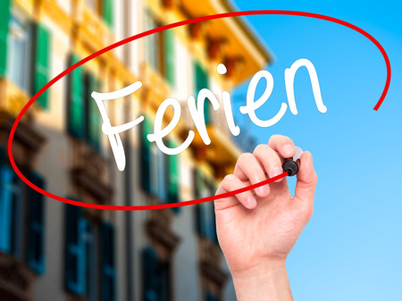 rescheduling: Man Hand writing Ferien  (Vacation in German) with black marker on visual screen. Isolated on background. Business, technology, internet concept. Stock Photo