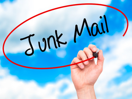 solicitors: Man Hand writing Junk Mail with black marker on visual screen. Isolated on sky. Business, technology, internet concept. Stock Photo