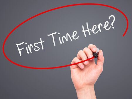 first time buyer: Man Hand writing First Time Here? with black marker on visual screen. Isolated on background. Business, technology, internet concept. Stock Photo