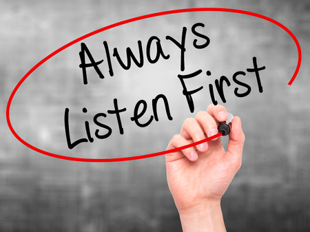 always listen first: Man Hand writing Always Listen First with black marker on visual screen. Isolated on grey. Business, technology, internet concept. Stock Photo