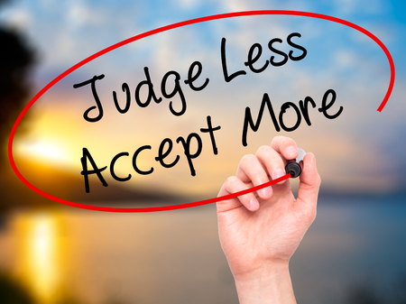 favoritism: Man Hand writing Judge Less Accept More with black marker on visual screen. Isolated on background. Business, technology, internet concept. Stock Photo