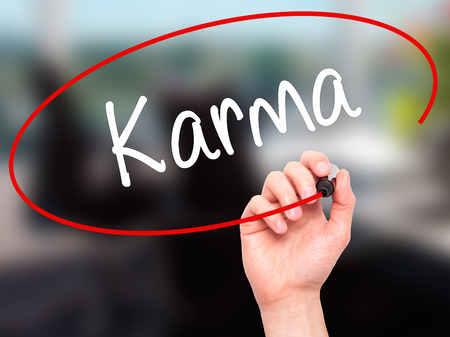 forthcoming: Man Hand writing Karma  with black marker on visual screen. Isolated on background. Business, technology, internet concept. Stock Photo