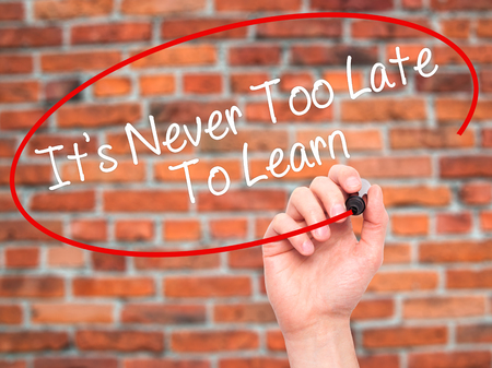 too late: Man Hand writing Its Never Too Late To Learn with black marker on visual screen. Isolated on background. Business, technology, internet concept. Stock Photo Stock Photo