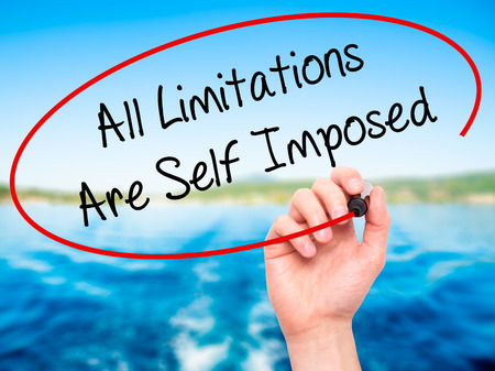 limitations: Man Hand writing All Limitations Are Self Imposed with black marker on visual screen. Isolated on background. Business, technology, internet concept. Stock Photo