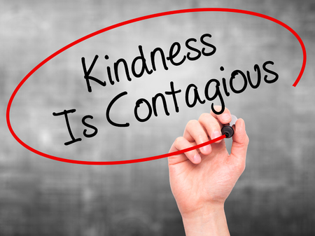Man Hand writing Kindness Is Contagious with black marker on visual screen. Isolated on background. Business, technology, internet concept. Stock Photo Stock Photo