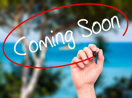 forthcoming: Man Hand writing Coming Soon with black marker on visual screen. Isolated on nature. Business, technology, internet concept. Stock Photo Stock Photo