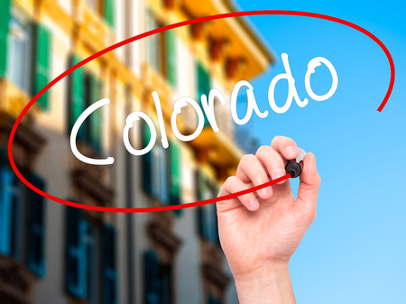 colorado city: Man Hand writing Colorado  with black marker on visual screen. Isolated on city. Business, technology, internet concept. Stock Photo