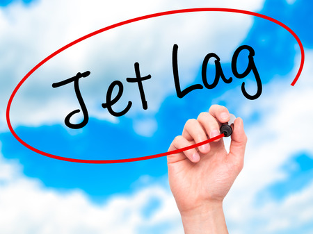 lag: Man Hand writing  Jet Lag with black marker on visual screen. Isolated on background. Business, technology, internet concept. Stock Photo Stock Photo