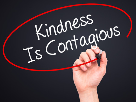 contagious: Man Hand writing Kindness Is Contagious with black marker on visual screen. Isolated on background. Business, technology, internet concept. Stock Photo Stock Photo