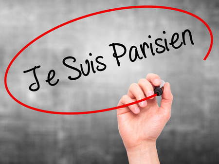 writing on screen: Man Hand writing Je Suis Parisien with black marker on visual screen. Isolated on grey. Stock Photo
