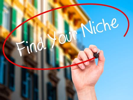 niche: Man Hand writing Find Your Niche with black marker on visual screen. Isolated on city. Business, technology, internet concept. Stock Photo
