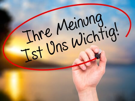 solicit: Man Hand writing Ihre Meinung Ist Uns Wichtig! (Your Opinion is Important to Us in German) with marker on visual screen. Isolated on background. Business, technology, internet concept. Stock Photo
