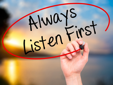 always listen first: Man Hand writing Always Listen First with black marker on visual screen. Isolated on nature. Business, technology, internet concept. Stock Photo