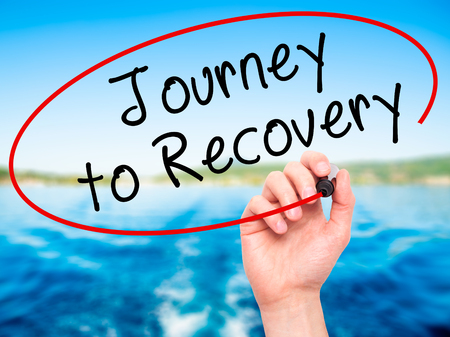 Man Hand writing Journey to Recovery with black marker on visual screen. Isolated on nature. Life, technology, internet concept. Stock Image
