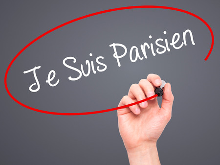 killed: Man Hand writing Je Suis Parisien with black marker on visual screen. Isolated on grey. Stock Photo