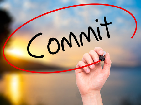 to commit: Man Hand writing Commit with black marker on visual screen. Isolated on background. Business, technology, internet concept. Stock Photo Stock Photo