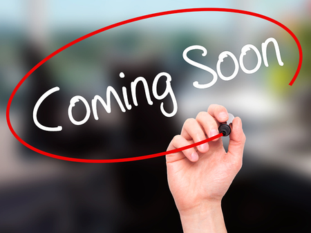 forthcoming: Man Hand writing Coming Soon with black marker on visual screen. Isolated on office. Business, technology, internet concept. Stock Photo Stock Photo