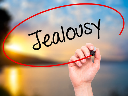envious: Man Hand writing Jealousy with black marker on visual screen. Isolated on nature. Business, technology, internet concept. Stock Photo
