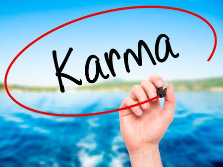 bad leadership: Man Hand writing Karma  with black marker on visual screen. Isolated on background. Business, technology, internet concept. Stock Photo