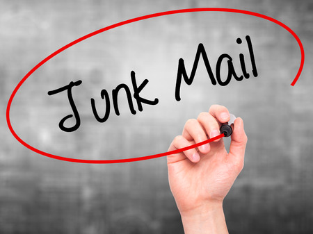 solicitors: Man Hand writing Junk Mail with black marker on visual screen. Isolated on grey. Business, technology, internet concept. Stock Photo