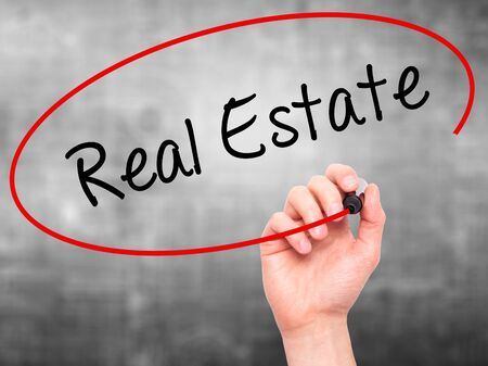 finer: Man Hand writing Real Estate  with black marker on visual screen. Isolated on grey. Business, technology, internet concept. Stock Photo Stock Photo