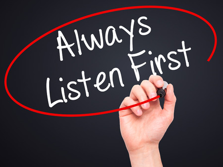 always listen first: Man Hand writing Always Listen First with black marker on visual screen. Isolated on black. Business, technology, internet concept. Stock Photo