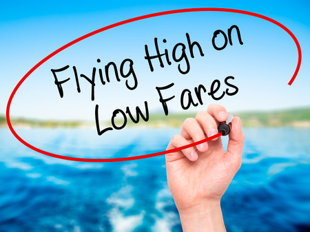 airplane ticket: Man Hand writing Flying High on Low Fares with black marker on visual screen. Isolated on background. Business, technology, internet concept. Stock Photo