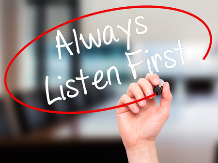 always listen first: Man Hand writing Always Listen First with black marker on visual screen. Isolated on office. Business, technology, internet concept. Stock Photo Stock Photo