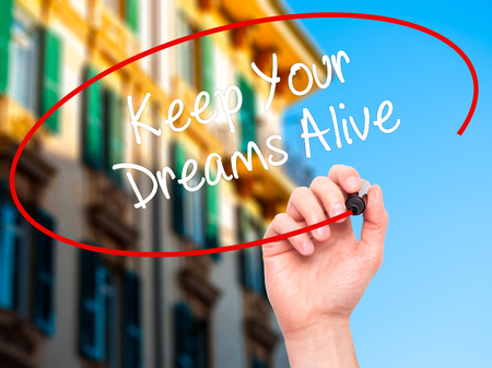 dreams of city: Man Hand writing Keep Your Dreams Alive with black marker on visual screen. Isolated on city. Business, technology, internet concept. Stock Photo