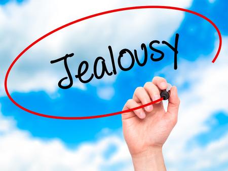 celos: Hombre de la mano escribiendo celos con marcador negro en la pantalla visual. Aislado en el cielo. Negocios, la tecnolog�a, el concepto de internet. Foto de stock