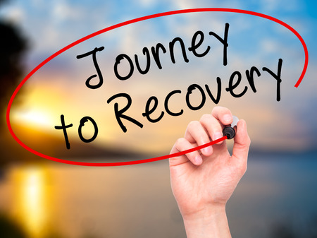 work addicted: Man Hand writing Journey to Recovery with black marker on visual screen. Isolated on nature. Life, technology, internet concept. Stock Image