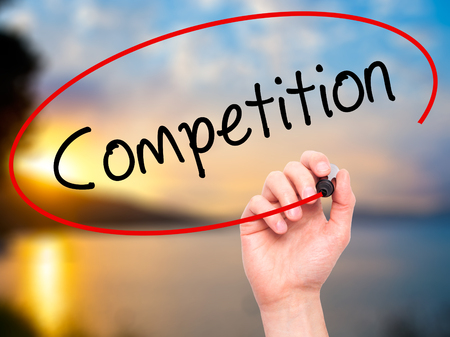 competitividad: Man Hand writing Competition  with black marker on visual screen. Isolated on background. Business, technology, internet concept. Stock Photo