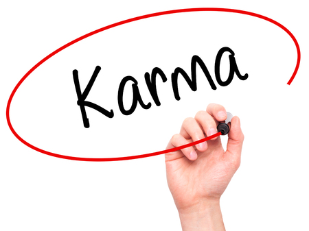 imminent: Man Hand writing Karma  with black marker on visual screen. Isolated on background. Business, technology, internet concept. Stock Photo
