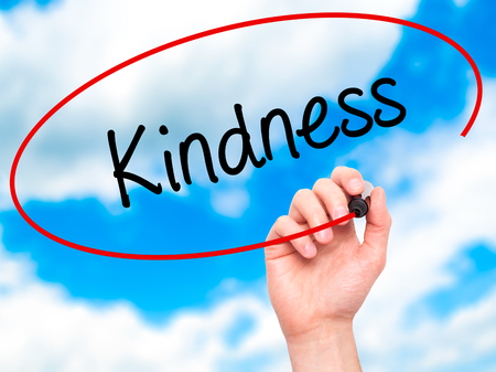 cordial: Man Hand writing Kindness with black marker on visual screen. Isolated on sky. Business, technology, internet concept. Stock Photo