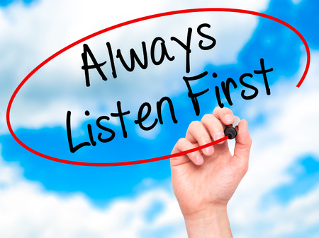 always listen first: Man Hand writing Always Listen First with black marker on visual screen. Isolated on sky. Business, technology, internet concept. Stock Photo