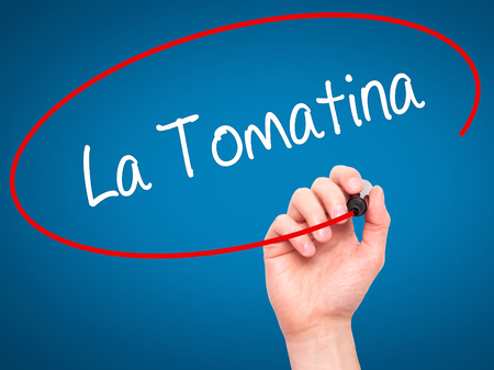 fiesta popular: Man Hand writing La Tomatina with black marker on visual screen. Isolated on blue. Business, technology, internet concept.