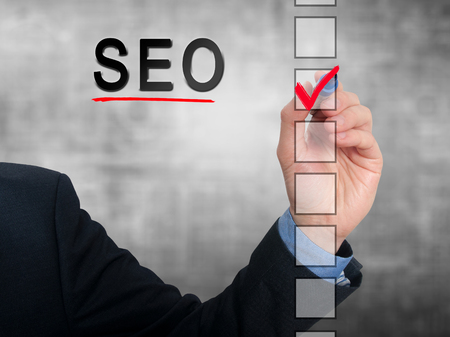 seo concept: businessman checking mark on SEO checklist marker. Checking SEO. Isolated on grey background, Stock Photo Stock Photo