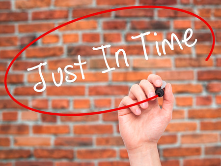 eliminating: Man Hand writing Just In Time with black marker on visual screen. Isolated on bricks. Business, technology, internet concept. Stock Photo Stock Photo