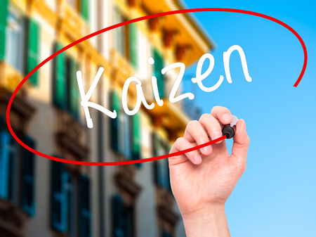 kaizen: Man Hand writing Kaizen with black marker on visual screen. Isolated on city. Business, technology, internet concept. Stock Photo