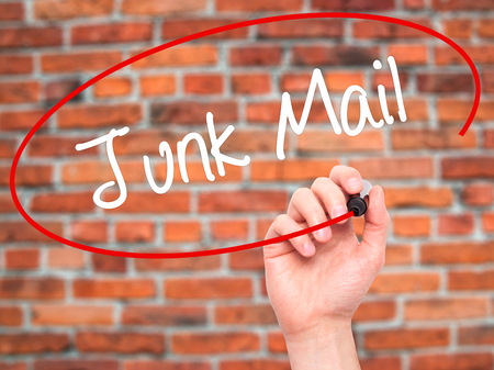 solicitors: Man Hand writing Junk Mail with black marker on visual screen. Isolated on bricks. Business, technology, internet concept. Stock Photo Stock Photo