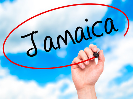 bob: Man Hand writing Jamaica  with black marker on visual screen. Isolated on sky. Business, technology, internet concept. Stock Photo
