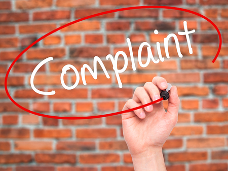 complaint: Man Hand writing Complaint with black marker on visual screen. Isolated on bricks. Business, technology, internet concept. Stock Image Stock Photo