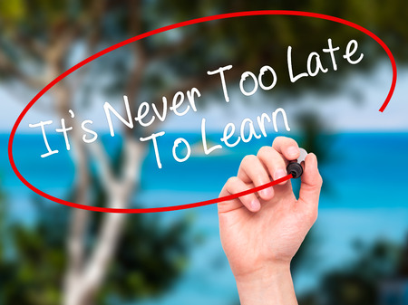intelligent partnership: Man Hand writing Its Never Too Late To Learn with black marker on visual screen. Isolated on background. Business, technology, internet concept. Stock Photo Stock Photo