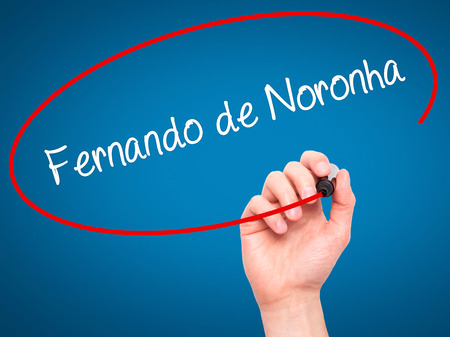 accommodating: Man Hand writing Fernando de Noronha with black marker on visual screen. Isolated on blue. Business, technology, internet concept. Stock Photo